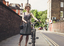 Woman Wearing Grey Dress Standing While Holding Bicycle Near Roadside and Grey Brick Wall during Daytime Stock Photo