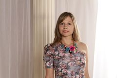 Woman Wearing Grey and Multicolored Floral Single-shoulder Top Against Beige Curtains royalty free stock image
