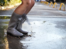 Woman wearing grey polka dots rain boots jumping into a puddle Stock Photo