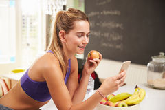 Woman Wearing Gym Clothing Looking At Mobile Phone Stock Images