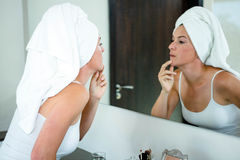 Woman wearing a  hair towel inspecting her skin Stock Images