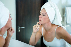 Woman wearing a  hair towel inspecting her skin Stock Image