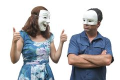 Woman wearing a happy face mask pointing thumbs up at a man who stock image