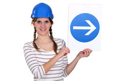 Woman wearing hard hat. And holding road sign Royalty Free Stock Photo