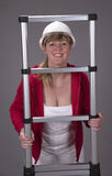 Woman wearing a hard hat and holding a telescopic ladder Royalty Free Stock Image
