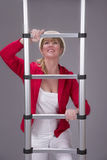 Woman wearing a hard hat and holding a telescopic ladder Royalty Free Stock Photos