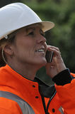 Woman wearing a hard hat using a phone Stock Photography