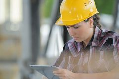 Woman wearing hardhat looking at tablet. Woman stock photo