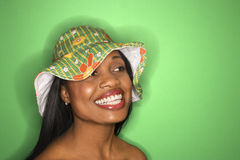 Woman wearing hat. Smiling African-American mid-adult woman wearing green hat on green background Stock Photography