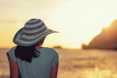 Woman wearing hat admire the sunset over the sea. On the beach stock images