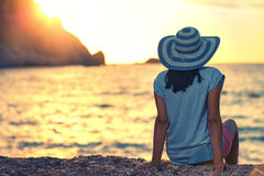 Woman wearing hat admire the sunset over the sea Stock Image