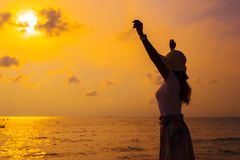 Woman wearing hat with arms raised standing on sea beach at sunset royalty free stock photos