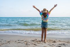 Woman wearing hat with arms raised standing on sea beach royalty free stock image