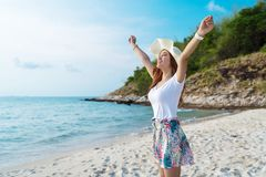 Woman wearing hat with arms raised standing on sea beach stock photos