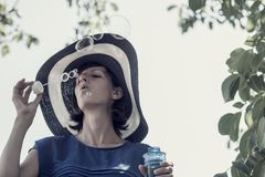 Woman wearing hat blowing bubbles under tree Royalty Free Stock Image