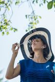 Woman wearing hat with blue dress blowing bubbles. Low angle view of woman wearing hat with blue dress blowing bubbles under tree Stock Photography