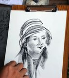 Woman wearing hat Charcoal drawing. Artist demonstrate fast painting a lady on paper Stock Photos