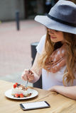 Woman wearing hat eating brakfast at table Stock Photos