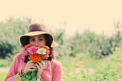 Woman Wearing Hat and Holding Flowers Surrounded by Plants Royalty Free Stock Photos