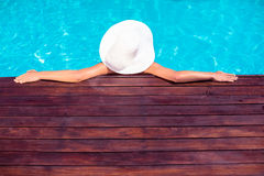 Woman wearing hat leaning on wooden deck by poolside Stock Photo