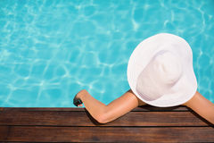 Woman wearing hat leaning on wooden deck by poolside Royalty Free Stock Photography