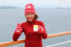 Woman wearing in hat and mittens holds cup of tea Stock Photography