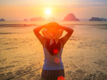 Woman wearing hat with open arms under the sunrise. Near the sea Stock Image