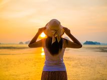 Woman wearing hat with open arms under the sunrise near by the sea. Travel and holiday concept Stock Photography