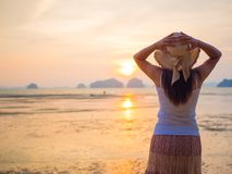 Woman wearing hat with open arms under the sunrise near the sea.  Royalty Free Stock Photos