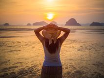 Woman wearing hat with open arms under the sunrise near the sea.  Royalty Free Stock Photography
