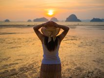 Woman wearing hat with open arms under the sunrise near the sea.  Royalty Free Stock Images