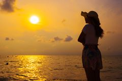 Woman wearing hat standing on sea beach at sunset royalty free stock photos