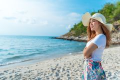 Woman wearing hat standing on sea beach royalty free stock photo