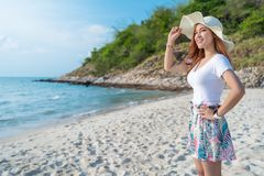 Woman wearing hat standing on sea beach stock photography