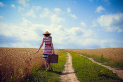 Woman wearing hat with suitcase on road in wheat Stock Photo