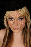 Woman wearing hat with veil. Portrait of pretty young blond woman wearing hat with veil, black background Royalty Free Stock Photography