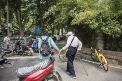 A woman wearing a hat and a walking stick wearing a white coat and a humpbacked elderly woman walking in the street. In the Qinhuai District, Nanjing, Jiangsu royalty free stock photography