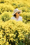 Woman wearing a hat with yellow flowers. stock images