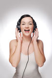 Woman wearing headphones. A pretty young woman wearing headphones and smiling/laughing in front of a grey and white background stock photos