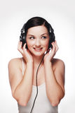 Woman wearing headphones. A pretty young woman wearing headphones and smiling/laughing in front of a grey and white background royalty free stock images