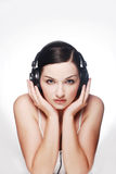 Woman wearing headphones. A pretty young woman wearing headphones looking at camera in front of a grey and white background stock images