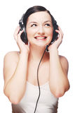 Woman wearing headphones. A pretty young woman wearing headphones and smiling/laughing in front of a grey and white background royalty free stock photography