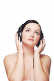 Woman wearing headphones. A pretty young woman wearing headphones looking upwards in front of a grey and white background stock photos