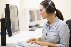Woman wearing headphones in computer room typing Royalty Free Stock Photos