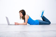 Woman wearing headphones lying on the floor with laptop. Smiling woman wearing headphones lying on the floor with laptop Royalty Free Stock Photo