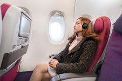Woman wearing headphones and sleeping in airplane in flight time. Woman wearing headphones and sleeping in an airplane in flight time stock photography
