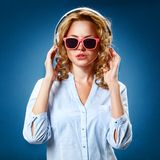 Woman wearing headphones and sunglasses Stock Images