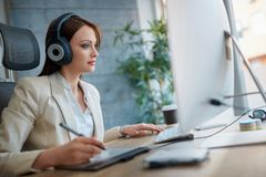 Woman wearing headphones and working in design studio. Young woman wearing headphones and working in design studio stock images