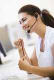 Woman wearing headset in computer room smiling Royalty Free Stock Photos