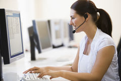 Woman Wearing Headset In Computer Room Smiling Royalty Free Stock Photography